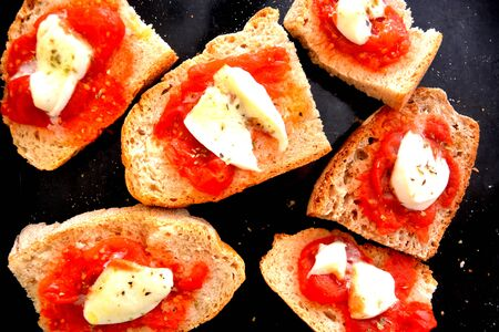group of various baked bruschettas with tomato and mozzarella typical italian food Archivio Fotografico