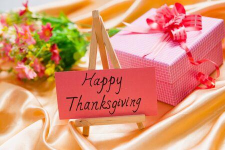 """silk cloth: carta carta con """"happy thanksgiving"""" su di esso, e la confezione regalo e fiori su un panno di seta Archivio Fotografico"""