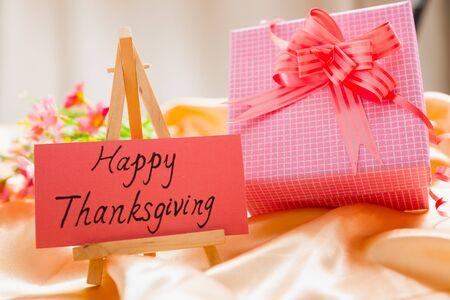 """seidenstoff: Papier-Karte mit """"Happy Thanksgiving"""" darauf und Geschenk-Box und Blumen auf einem Seidentuch Lizenzfreie Bilder"""