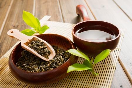 hojas de te: t� y hojas de t� en la estera de bamb� en mesa de madera