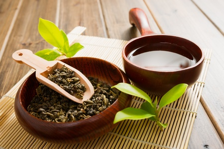 tea and tea leaves on bamboo mat on wooden table photo
