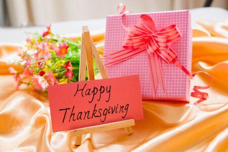 tissu soie: papier cartonn� avec thanksgiving heureux sur elle, et bo�te-cadeau et des fleurs sur un tissu de soie