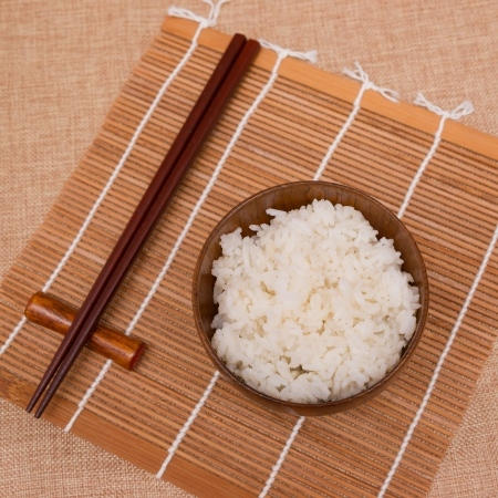 tradional: rice in a wooden bowl on bamboo mat Stock Photo