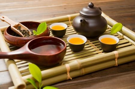 tazza di th�: teiera, tazza di t� e foglie di t� su una stuoia di bamb�