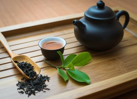 Teeblätter, Teetasse und Teekanne auf dem Bambus-Matte Standard-Bild - 19936840