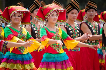 Nanning, China - 24. März 2012: Chinesisches Mädchen tanzen in der Zhuang ethnischen Festival.March 3. ist der Songs Festival der ethnischen Zhuang im Südwesten China.Every Jahr an diesem Tag, Zhuang ethnischen Menschen mit traditionellen Kleid Gesang und Tanz zu feiern thi Standard-Bild - 19995780