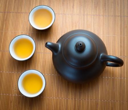 bamboo mat: pottery teapot and teacup on bamboo mat