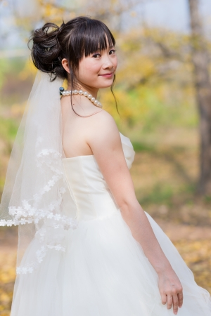 chinese dress: happiness bride in ginkgo forest Stock Photo