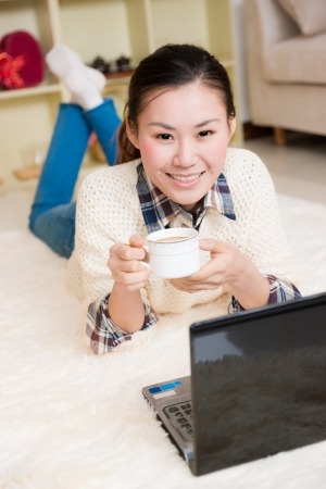 young asian woman using a laptop with smile at home photo