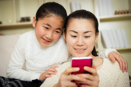 mother and daughter using a smart phone at home