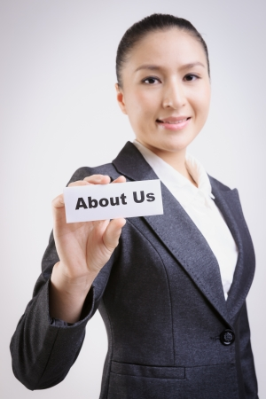 about us: business woman with a paper card with about us on it