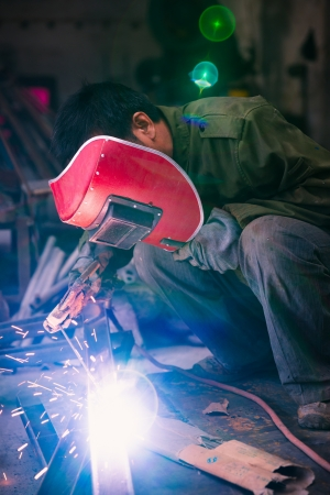 Chinese worker welding metal in a workshop photo
