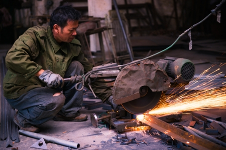 Chinese worker cutting industrial materials with machine  in a workshop photo