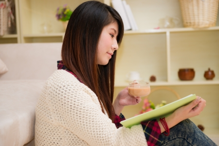 young asian woman reading book at home photo