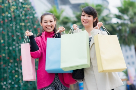 happy Chinese women with shopping bags in business street photo