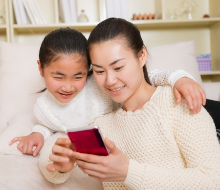 mother and daughter using a smart phone at home photo
