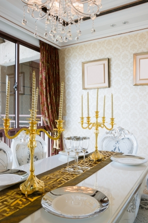 nice tableware and candlesticks on dining table photo