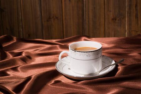 tela seda: una taza de café con el fondo marrón de tela de seda Foto de archivo