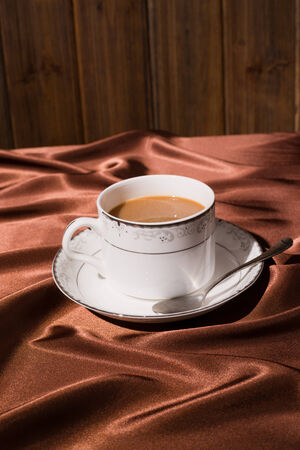 seidenstoff: eine Tasse Kaffee mit braunem Seidentuch Hintergrund
