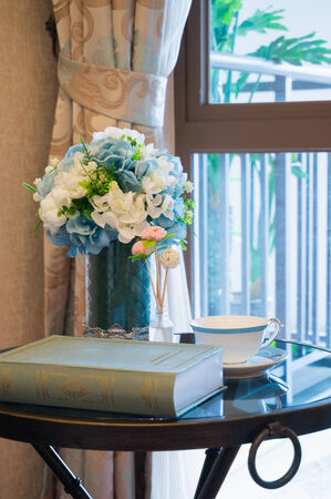 side table: book,teacup and flower vase on side table beside the window Stock Photo