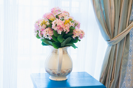 side table: flower with vase on side table beside the window