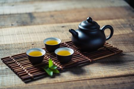 Taza de té y tetera en tabla de madera Foto de archivo - 73139209