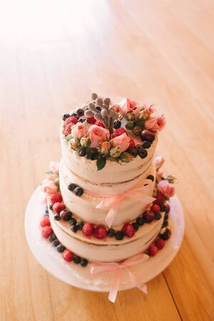 Beautiful white cream wedding cake decorated with fresh strawberries, blueberries and pink roses on wooden background