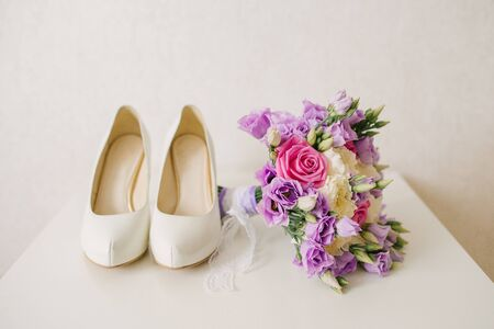 The brides shoes and pink lilac wedding bouquet lies next to the white background, the brides accessories Banco de Imagens