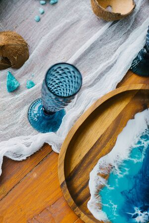 serving plate made of wood with a pattern of epoxy resin drawing of the sea, standing next to a blue glass glass. Banquet table in the style of the sea Banco de Imagens