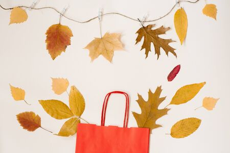 Autumn shopping with discounts. A red paper shopping bag with autumn yellow leaves peeking out of it. Copy space. Autumn sales. The thread on primako hanging leaves Foto de archivo - 129923968
