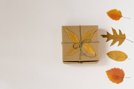 craft gift box, tied with string with a bow and autumn fallen leaves on a beige background. Yellow and red leaves. Autumn shopping discounts. Copy space Foto de archivo - 129924037