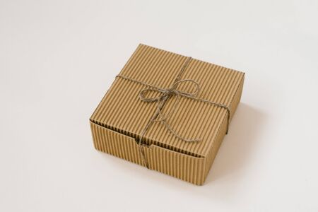 craft gift box tied with twine with on beige background. Gift wrap for birthday in natural style