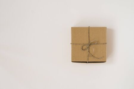 craft gift box tied with twine with on beige background. Birthday gift wrap. Copy space 스톡 콘텐츠