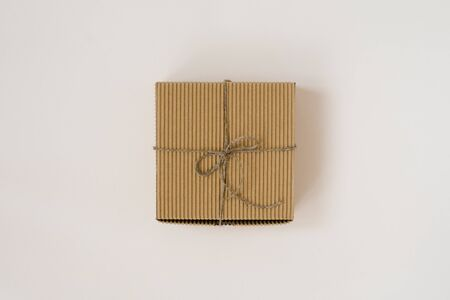 craft gift box tied with twine with on beige background. Birthday gift wrap. 스톡 콘텐츠