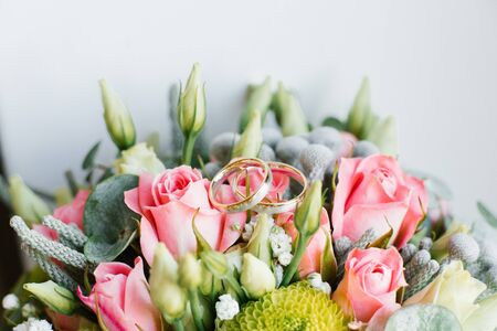 Gold wedding rings lie on the bride's wedding bouquet of roses, eustoma, eucalyptus. Close up. Copy space Stock Photo