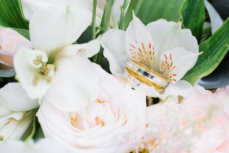 Wedding engagement rings of yellow and white gold are on the wedding bouquet, white flowers
