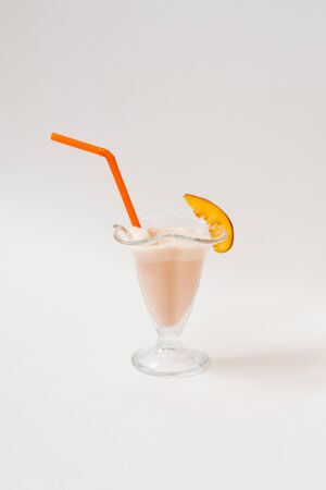 Milkshake with peaches or nectarine in a glass glass with orange straws and a piece of nectarine on the rim of the glass on a white background. Organic food and menu concept