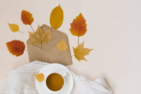 Kraft envelope with autumn yellow leaves, a white porcelain Cup with black tea and a knitted white plaid on a beige background, top view. Copy space. Hogge, autumn lay flat.