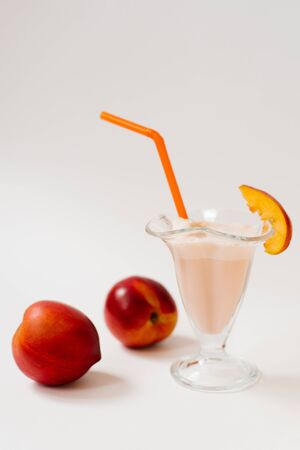 Milkshake with fresh nectarines in a glass glass with an orange plastic tube, next to two organic nectarines on a white background Imagens