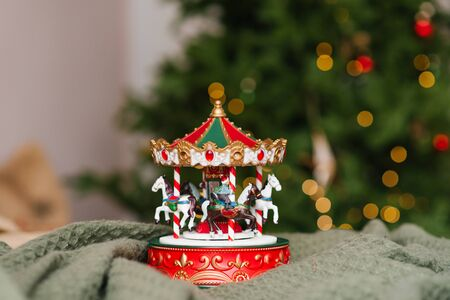 Childrens toy carousel on the background of a Christmas tree with burning lights