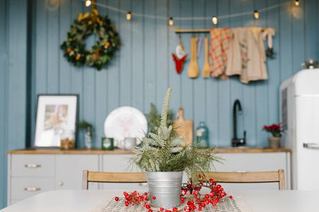 Branches ate in a metal vase on the kitchen table, decorated for Christmas and New Year