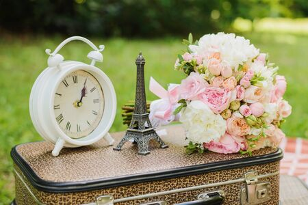 Table white clock, a statuette of the Eiffel tower, the brides bouquet are on the suitcase. Wedding decor