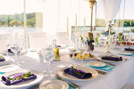 Tavolo per banchetti con servizio nuziale e festivo nei colori bianco blu e viola