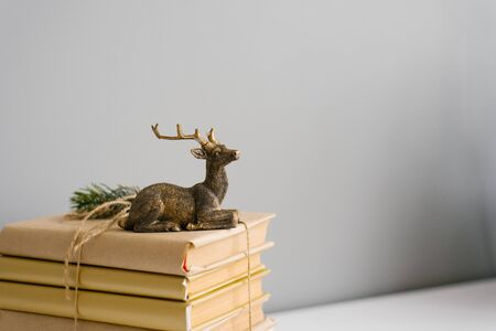 A stack of books in crane paper and a statuette of a sitting deer on a gray background. Copy space 写真素材
