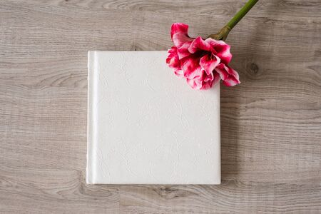 Wedding photo book in lace leather cover on beige background and bright pink flower next to it Stock Photo