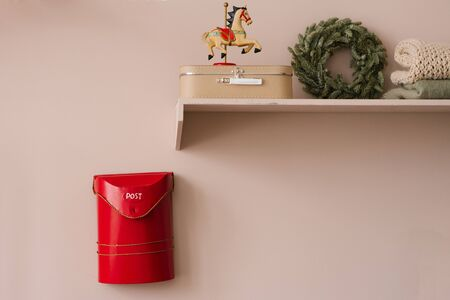 Mailbox for Santa Claus red and shelf with Christmas Souvenirs in the interior of the living room