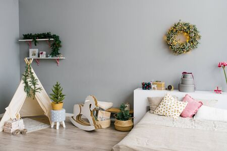 The interior of the bedroom or childrens room decorated for Christmas or New Year: bed, wigwam, childrens swing horse, Christmas wreath on the wall Zdjęcie Seryjne