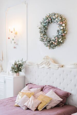 Pink and white Christmas decor in the classic bedroom, pillows on the bed and a wreath over the bed
