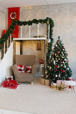 Traditional classic Christmas tree and beige armchair, stairs to the second floor in the living room or dining room in the house