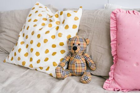 Soft toy plaid bear among pillows on the bed